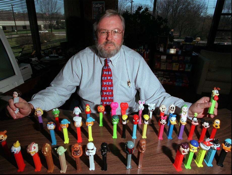 Scott McWhinnie, then-president of the Pez Company in Orange, poses in his office in 1999 with a few of current Pez Dispensers on the market. Photo: Hearst Connecticut Media File / NEW HAVEN REGISTER