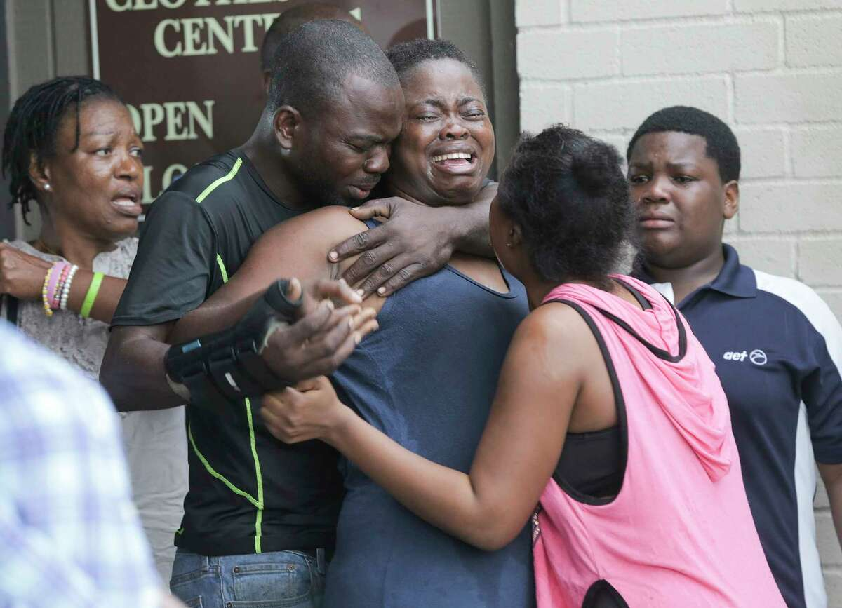 The mother of two young children, a 1-year-old girl and an 8-year-old boy, is comforted by her family after she found their bodies in their father's apartment on Saturday, Aug. 4, 2018 in Houston. Jean Pierre Ndossoka was charged with capital murder in the deaths.
