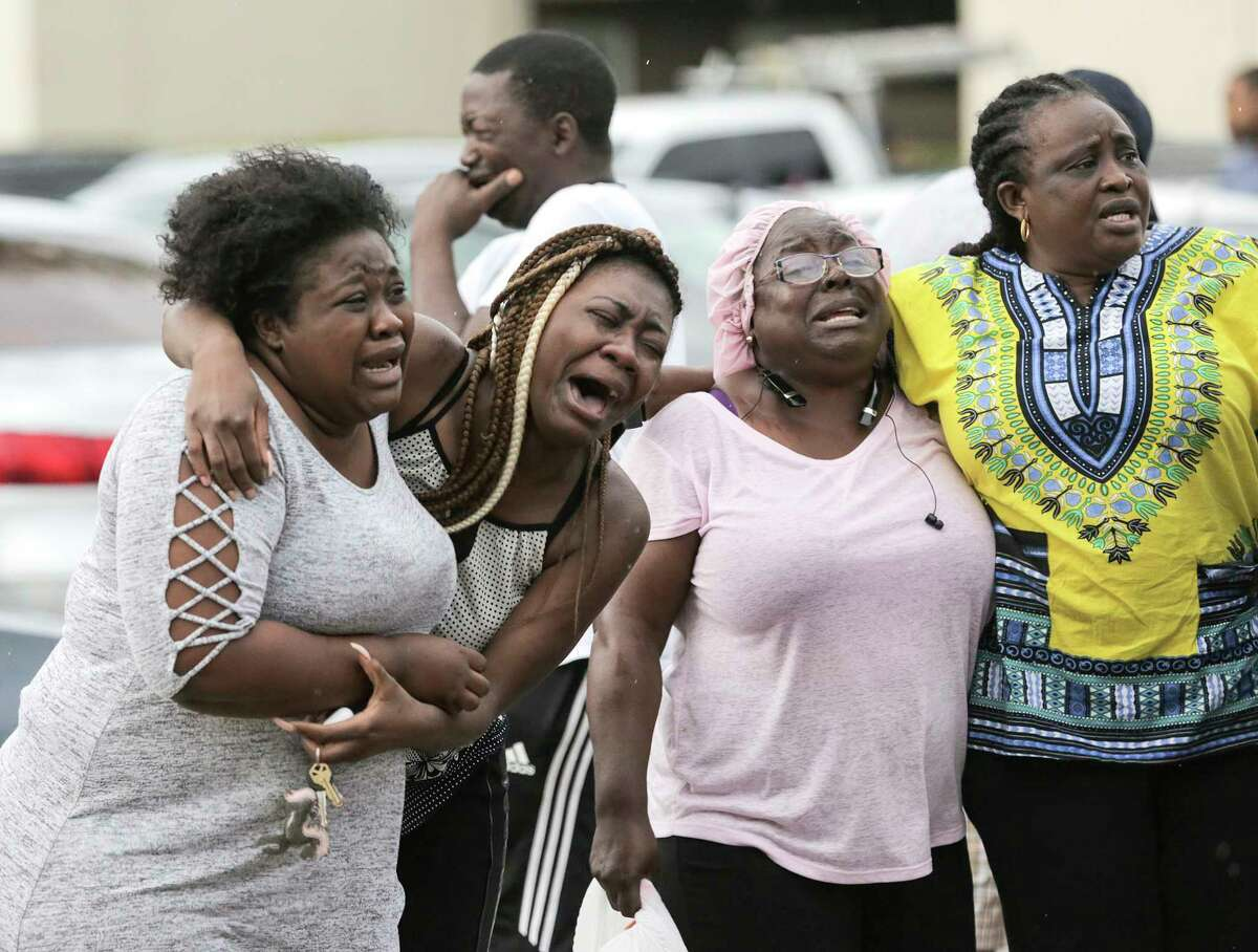 Neighbors and family members react to the news of two children, 1 and 8 years old, who were murdered in their father's apartment on Saturday, Aug. 4, 2018 in Houston.  Jean Pierre Ndossoka was charged with capital murder in the deaths.