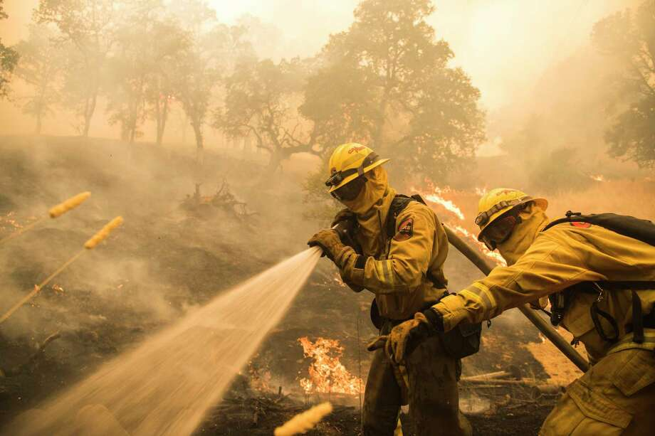 Firefighters worked to extinguish flames as the River Fire advanced toward structures west of Lakeport, Calif., on Tuesday. Photo: Photo For The Washington Post By Stuart W. Palley / Stuart W. Palley