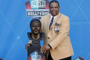 Former NFL player Robert Brazile poses with a bust of himself during inductions at the Pro Football Hall of Fame on Saturday, Aug. 4, 2018, in Canton, Ohio. (AP Photo/Gene J. Puskar)