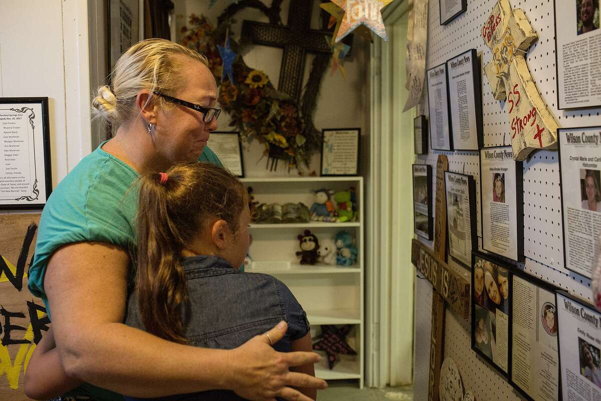 Robinn Alvizo embraces her daughter, Lillian Alvizo, 9, as they view the obituaries for victims, provided by the Wilson County News, in the Memorial Gallery on it's opening day at the Sutherland Springs Historical Museum on Saturday, August 4, 2018. Alvizo and her daughter were friends with some of the victims of the shooting.