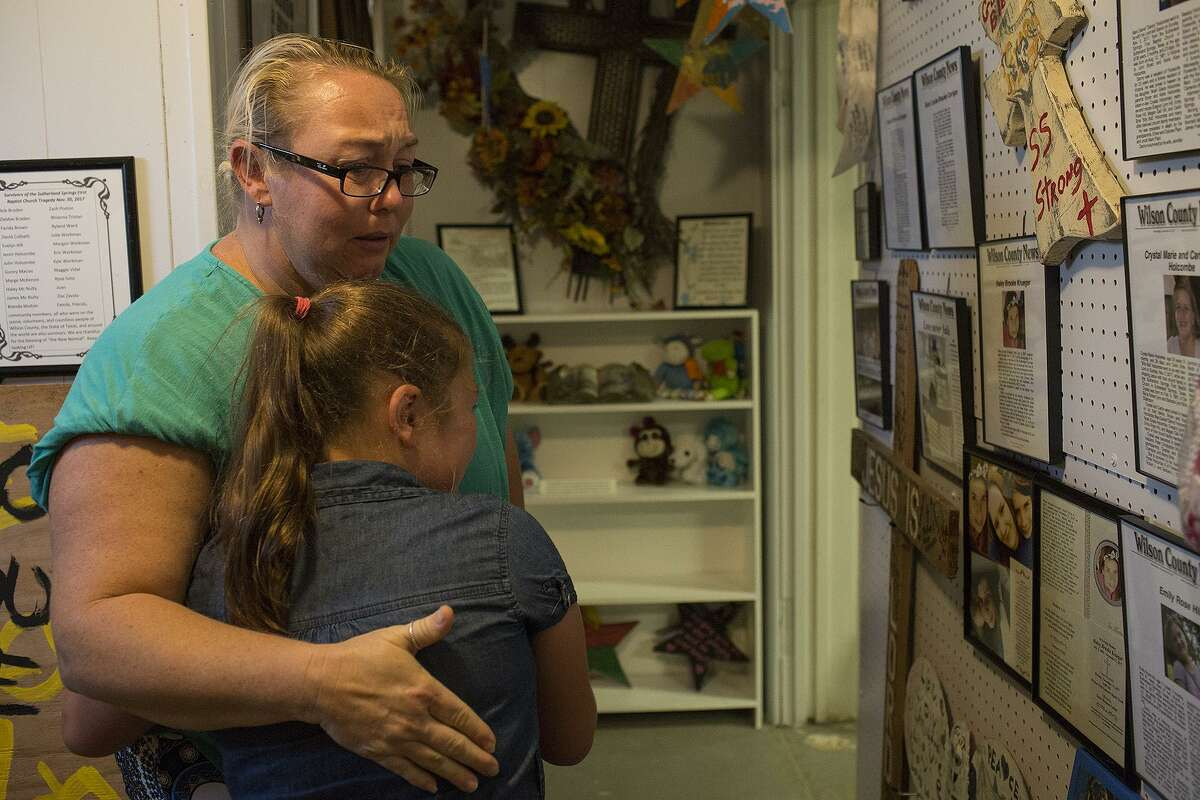 Robinn Alvizo embraces daughter Lillian Alvizo, 9, as they view obituaries of victims of the mass shooting at First Baptist Church of Sutherland Springs in the memorial gallery of the town's historical museum. The pair were friends of some of the victims.