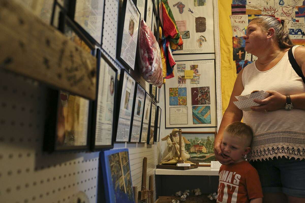 Sherri Osborn and her son, William Osborn, 3, view the Memorial Gallery on it's opening day at the Sutherland Springs Historical Museum on Saturday, August 4, 2018. Sherri's mother attends the church regularly but had stayed home with William, who was sick, while Sherri was out of town the day of the shooting.