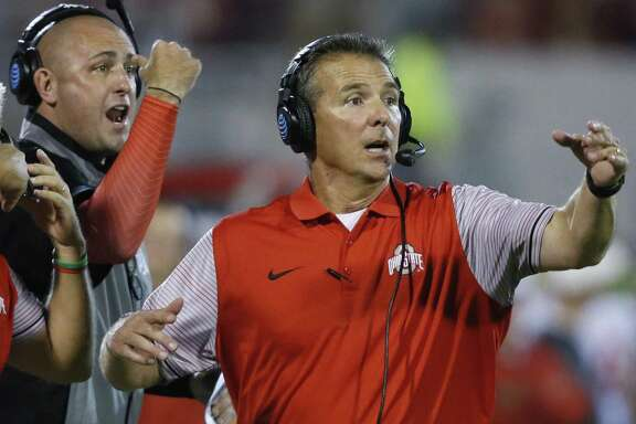 Urban Meyer (right), placed on paid administrative leave by Ohio State, revealed Friday he was aware of former assistant Zach Smith's domestic violence history and said he told the OSU brass.