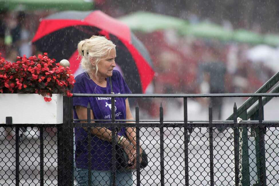 A racing patron endures the rains while waiting for #6 Diversify with jockey Irad Ortiz Jr. to go wire to wire winning 91st running of The Whitney Stakes Saturday Aug. 4, 2018 in Saratoga Springs, N.Y.(Skip Dickstein/Times Union)