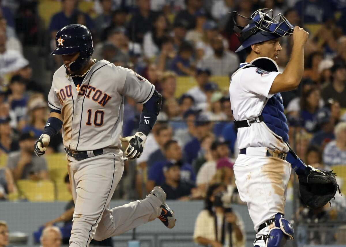 Houston Astros' Yuli Gurriel (10) crosses the plate behind Los Angeles Dodgers catcher Austin Barnes, right, during the sixth inning of a baseball game Saturday, Aug. 4, 2018, in Los Angeles. (AP Photo/John McCoy)
