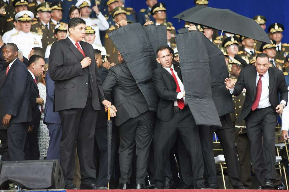 Security personnel surround President Nicolas Maduro with shields after an explosive detonated while he was giving a speech Saturday to soldiers in Caracas. He was unharmed. Photo: Xinhua News Agency