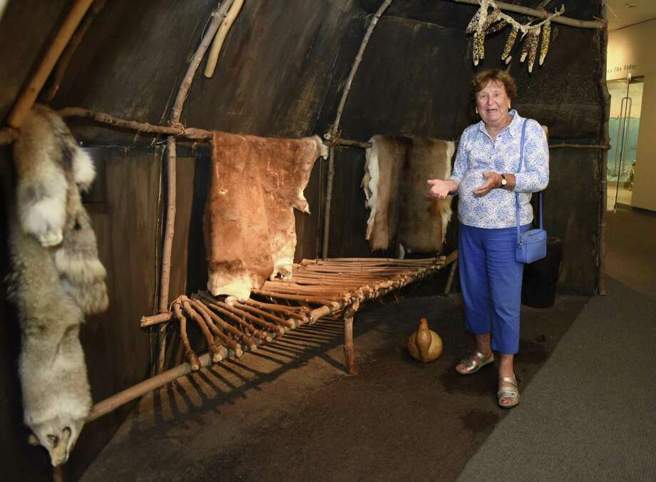 Volunteer docent Ursula Van Aken steps inside a wigwam on display from a Native Americans exhibit at the Bruce Museum in Greenwich, Conn. Thursday, Aug. 2, 2018. The Bruce Museum has more than 50 docents who volunteer their time to lead tours to groups of students and young children. Photo: Tyler Sizemore / Hearst Connecticut Media / Greenwich Time