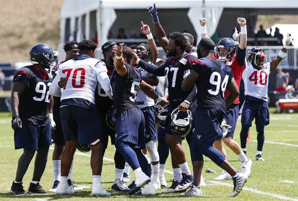 Houston Texans players mob defensive tackle Kingsley Opara after he caught a punt to end practice during training camp at the Greenbrier Sports Performance Center on Sunday, Aug. 5, 2018, in White Sulphur Springs, W.Va.