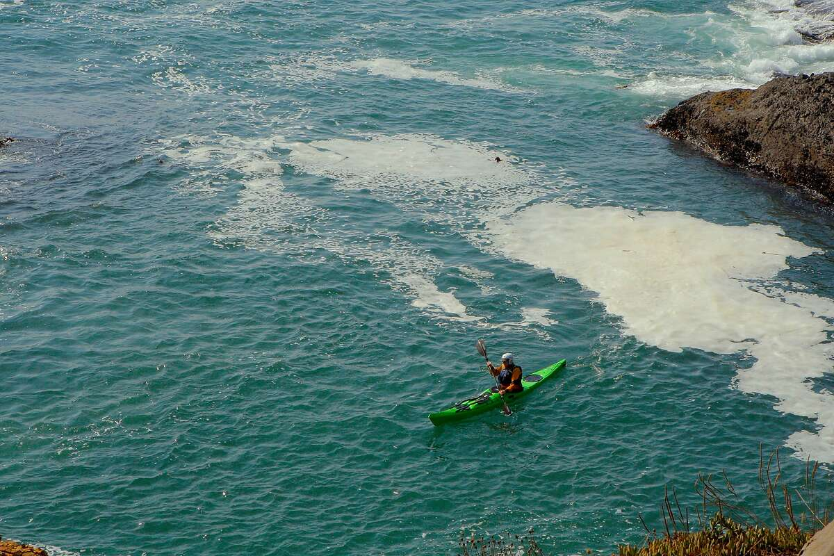 A kayaker paddles and plays in the swirling current of an eddy at the Mendocino Headlands