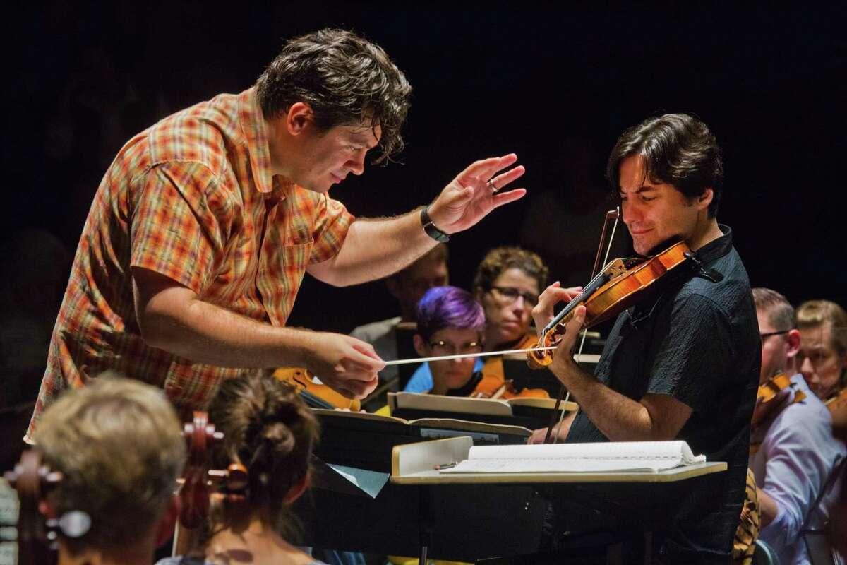 Conductor Cristian Macelaru rehearses with violin soloist Philippe Quint at the Cabrillo Festival of Contemporary Music. The Santa Cruz festival runs through Sunday, Aug. 12.