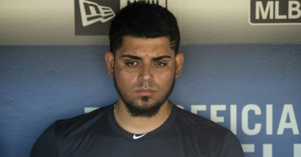 Houston Astros relief pitcher Roberto Osuna is interviewed in the dugout before a baseball game against the Los Angeles Dodgers in Los Angeles, Sunday, Aug. 5, 2018. Osuna served a 75-game suspension for violating Major League Baseball's domestic violence policy. (AP Photo/Kyusung Gong)