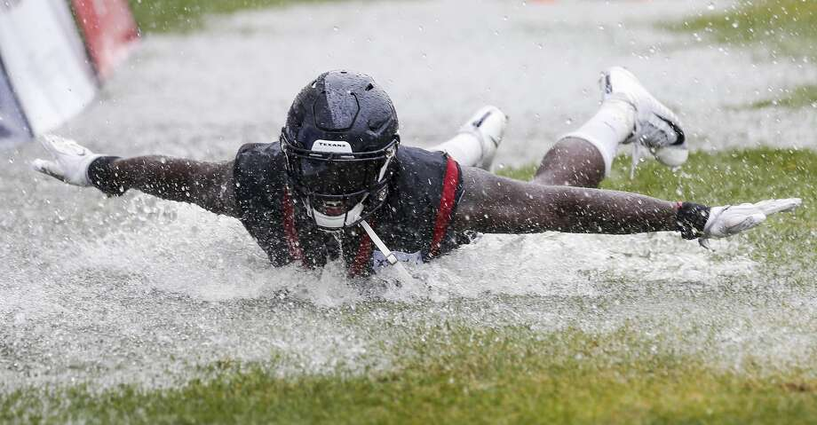 Houston Texans linebackers Whitney Mercilus (59) slides in a puddle of water on the field at the end of practice during training camp at the Greenbrier Sports Performance Center on Friday, Aug. 3, 2018, in White Sulphur Springs, W.Va. A steady rain fell throughout practice. Photo: Brett Coomer/Houston Chronicle