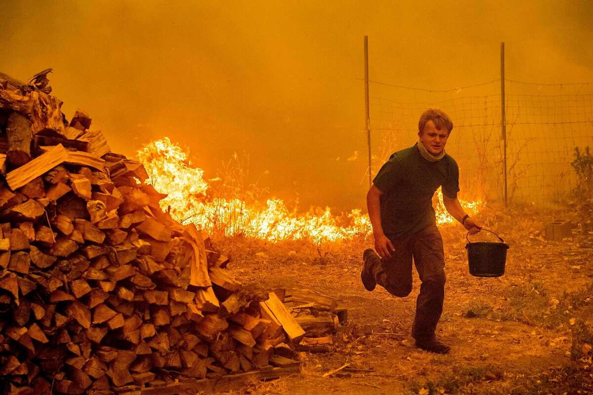 TOPSHOT - Alex Schenck carries a water bucket while fighting to save his home as the Ranch Fire tears down New Long Valley Rd near Clearlake Oaks, California, on Saturday, August 4, 2018. The Ranch Fire is part of the Mendocino Complex, which is made up of two blazes, the River Fire and the Ranch Fire. / AFP PHOTO / NOAH BERGERNOAH BERGER/AFP/Getty Images