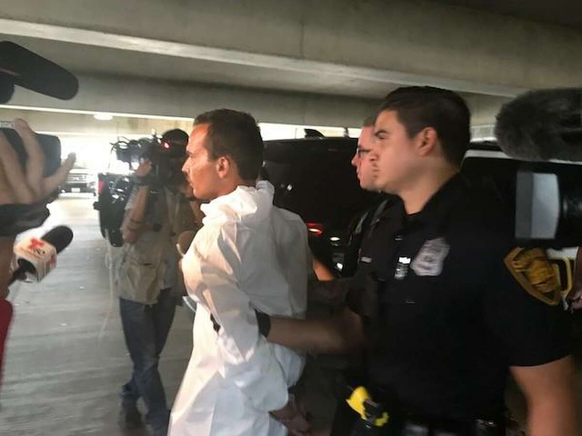Jacob Gabriel, 23, is taken to a San Antonio police squad car in handcuffs hours Sunday afternoon after he allegedly stole a car and fatally shot a witness who had pursued him.