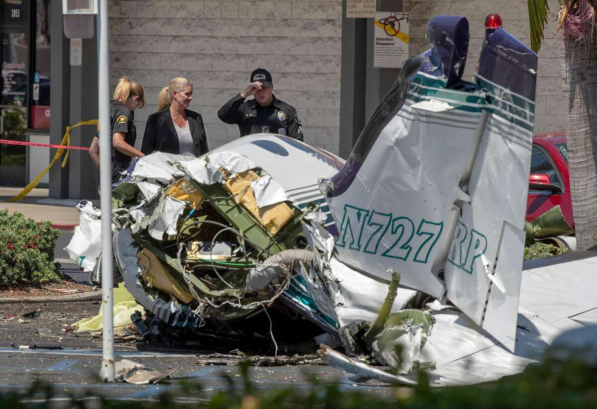 Orange County Sheriff's and Santa Ana Police investigators view the scene where five people were killed in a Cessna plane crash in a parking lot near the intersection of Bristol and Sunflower streets near South Coast Plaza in Santa Ana, Calif., on Sunday, Aug. 5, 2018. (Allen J. Schaben/Los Angeles Times/TNS)