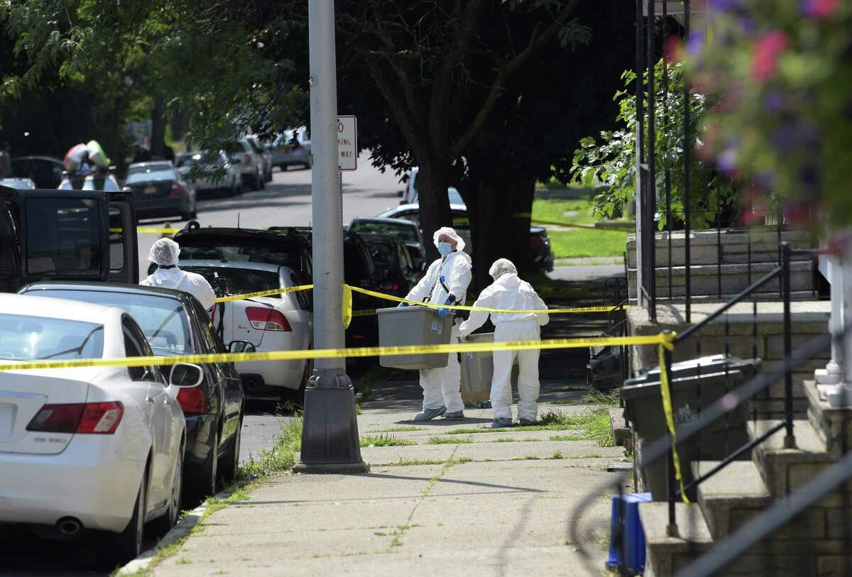 Crime scene technicians make their way into a home on Remsen Street where a shooting took place on Sunday, Aug. 5, 2018, in Cohoes, N.Y. (Paul Buckowski/Times Union)