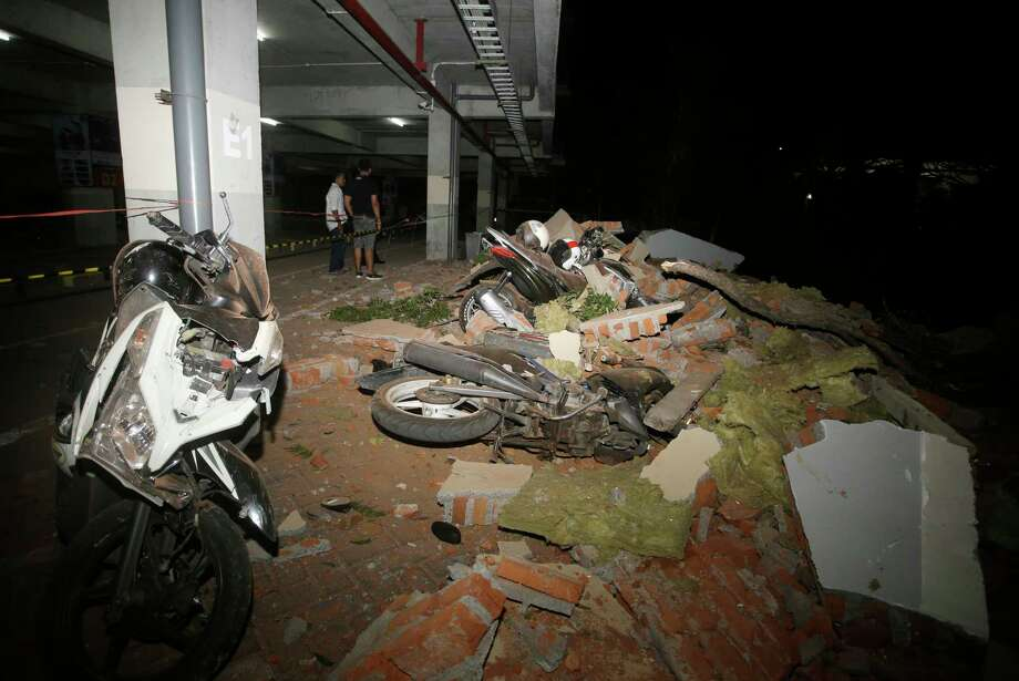 Debris on top of a motorcycles after an earthquake in Bali, Indonesia, Sunday, Aug. 5, 2018. A strong earthquake struck the Indonesian tourist island of Lombok on Sunday, killing at least three people and shaking neighboring Bali, one week after another quake on Lombok killed more than a dozen. (AP Photo/Firdia Lisnawati) Photo: Firdia Lisnawati / Copyright 2018 The Associated Press. All rights reserved.