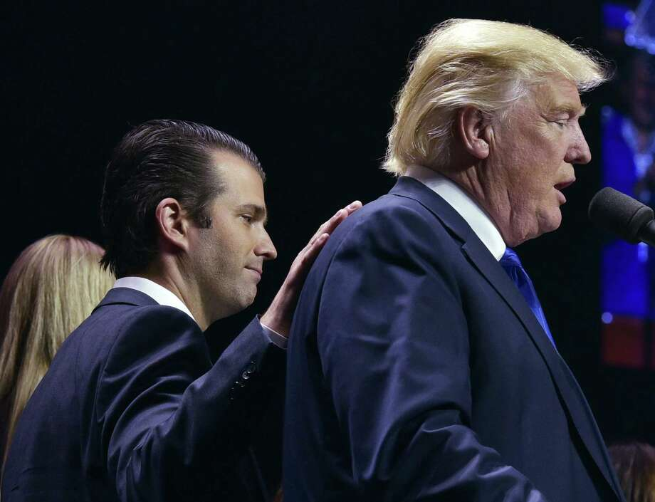 "(FILES) In this file photo taken on November 7, 2016 Donald Trump, Jr., (L) places a hand on the shoulder of his father, Republican presidential nominee Donald Trump, during in a rally on the final night of the 2016 US presidential election in Manchester, New Hampshire. President Trump denied on July 27, 2018, knowing about a 2016 meeting between top members of his election campaign team and a Russian lawyer, disputing reported claims by his former attorney, Michael Cohen. ""I did NOT know of the meeting with my son, Don jr,"" Trump said in a tweet. / AFP PHOTO / MANDEL NGANMANDEL NGAN/AFP/Getty Images Photo: MANDEL NGAN / AFP or licensors"