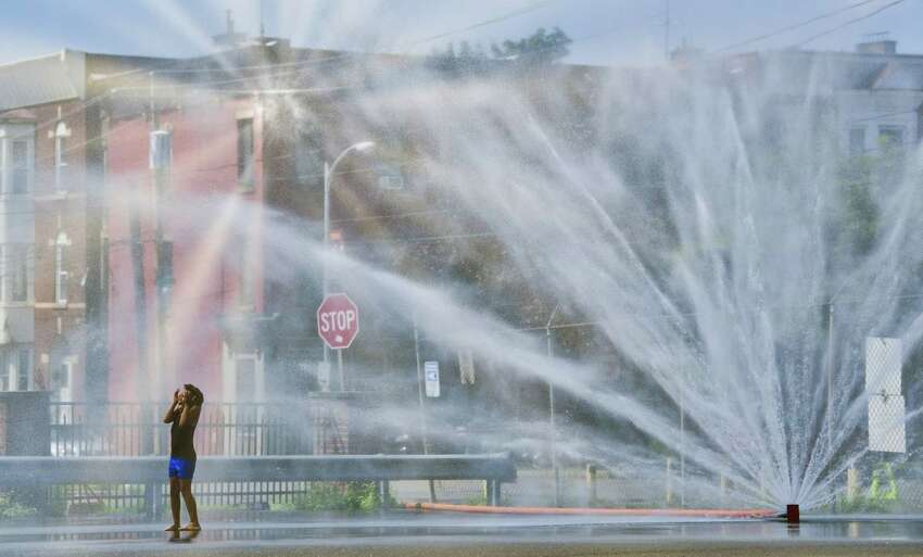 Faith Jett, 7, stands in a spray of water at the cooling off station in a lot at the corner of Liberty Street and Hill Street on Sunday, Aug. 5, 2018, in Troy, N.Y. The city of Troy has set up several cooling off stations for this week due to the heat and humidity. (Paul Buckowski/Times Union)