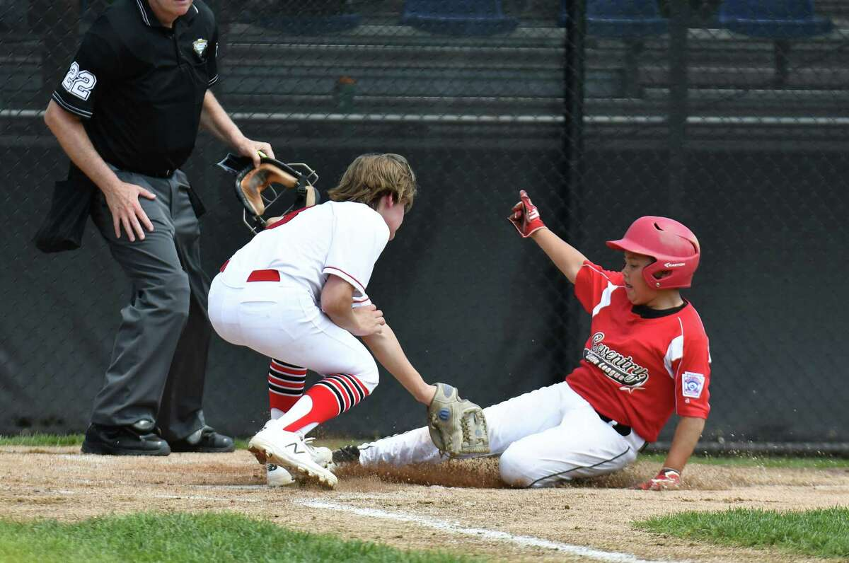 Pierce Cowles (8) of Fairfield American (CT) tags out a runner at home plate during the 2018 Little League Eastern Regional game against Coventry, Rhode Island on Sunday Aug 5, 2018, at the A. Bartlett Giamatti Little League Center in Bristol, Connecticut.