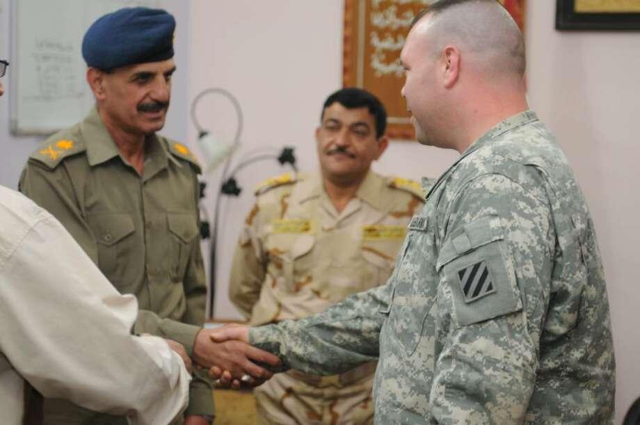Army Maj. Chris Auclair, right, of Georgia, formerly of Latham, briefs Maj. Gen. Qassim Atta, commander of the Iraqi Field Artillery School at Abu Ghrab. Auclair earned a Bronze Star during his first Iraq war tour.