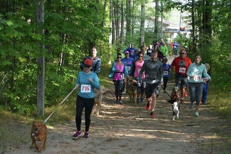 Runners and their dogs participate in a previous SOS Animal Rescue's Dirty Dog Trail Run at Midland City Forest. (Photo provided)