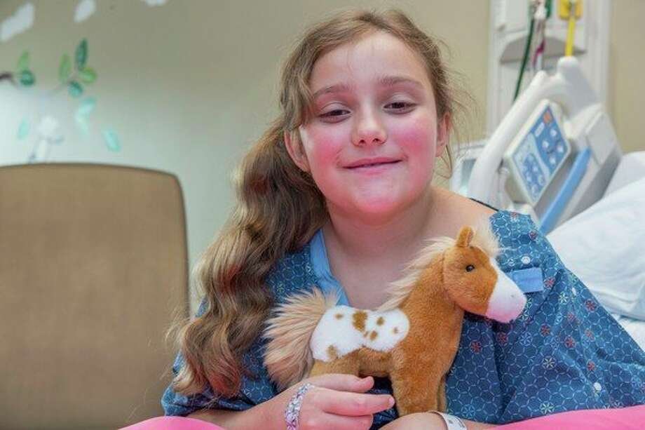 Lily VanConant-Eubank, from Midland, cradles one of the numerous stuffed animals purchased through funds donated by The Alden and Vada Dow Family Foundations. (Photo provided)