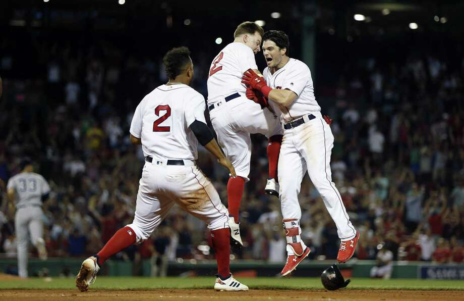 Andrew Benintendi, right, celebrates his game-winning RBI single with Brock Holt, center, and Xander Bogaerts (2) during the 10th inning on Sunday night. Photo: Michael Dwyer / Associated Press / Copyright 2018 The Associated Press. All rights reserved