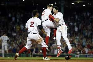 Andrew Benintendi, right, celebrates his game-winning RBI single with Brock Holt, center, and Xander Bogaerts (2) during the 10th inning on Sunday night.