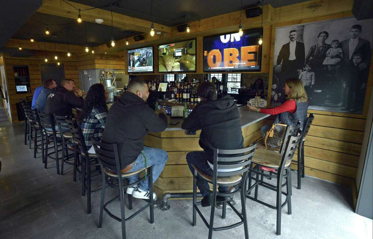 Patrons of Riko's Pizza cozy up to the bar at their newest location on Hope Street in Stamford on Oct. 13, 2016.