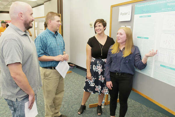 Maria Brauer, left, a rising junior from Belmont University, and Jennifer McBride, a rising junior from SIUE, present their findings at the REU Symposium.