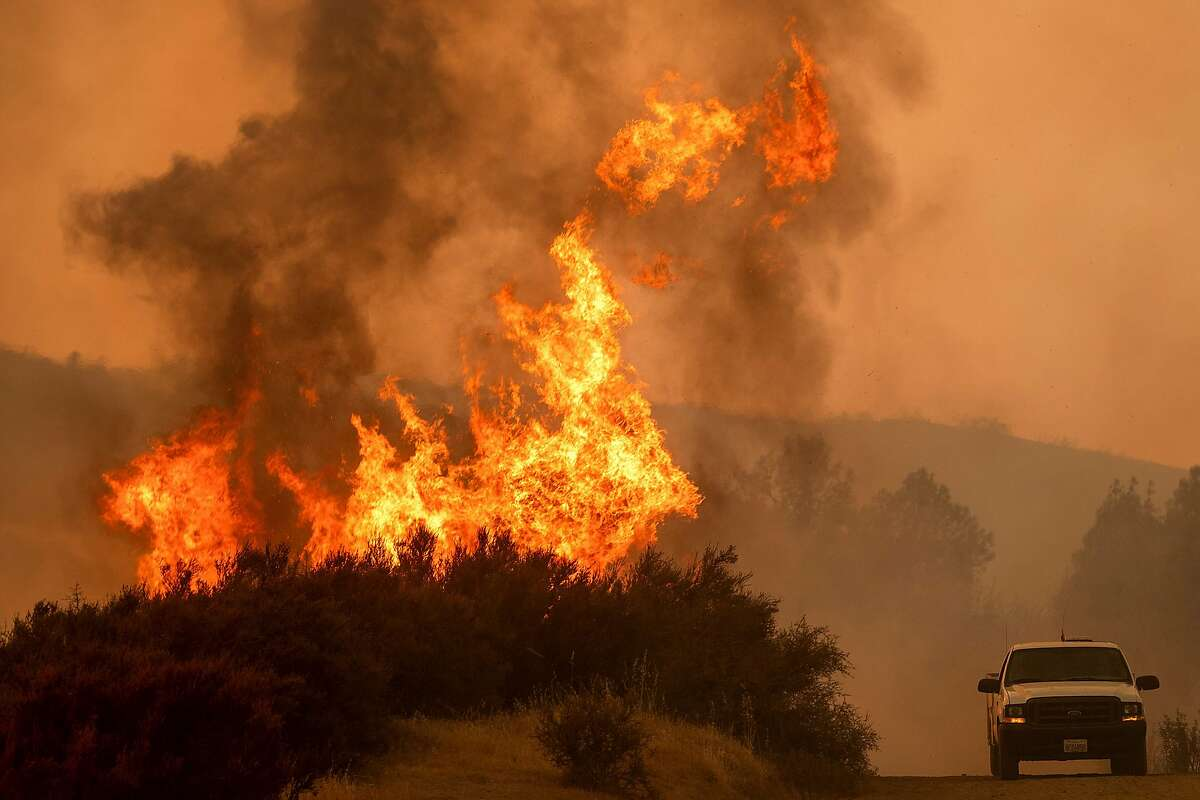 Flames leap above a vehicle on High Valley Rd as the Ranch Fire, part of the Mendocino Complex Fire, burns near Clearlake Oaks, California, on August 5, 2018. Several thousand people have been evacuated as various fires swept across the state, although some have been given permission in recent days to return to their homes.