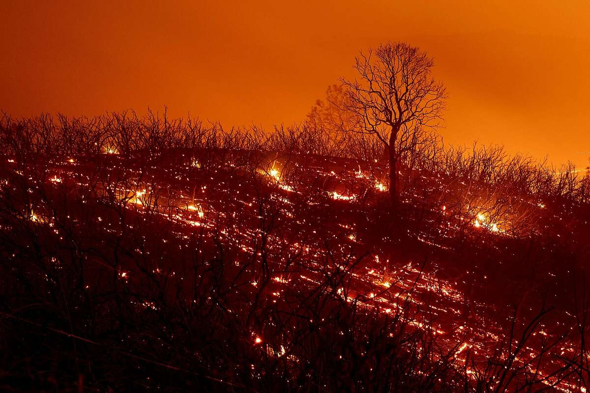 Embers smolder along a hillside after the Ranch Fire, part of the Mendocino Complex Fire, burned though the area near Clearlake Oaks, California, on August 5, 2018. - Several thousand people have been evacuated as various fires swept across the state, although some have been given permission in recent days to return to their homes.