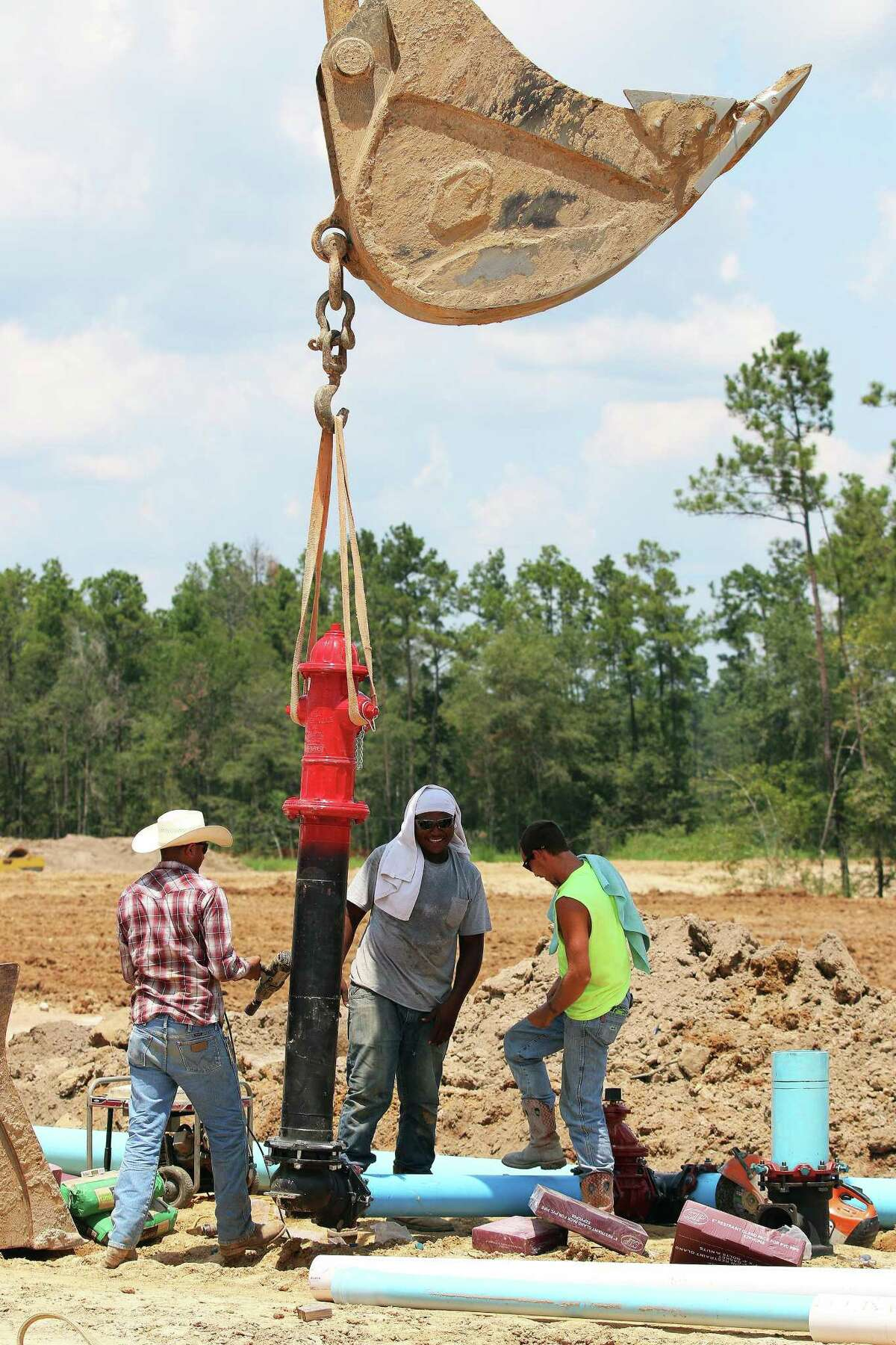 Contractors carefully maneuver one of the many fire hydrants for the Grand Oaks Reserve subdivision to be placed into the ground and connected to underground infrastructure.