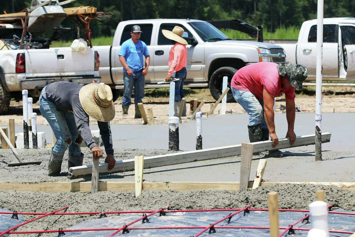 Workers do the tedious work of smoothing out the concrete that will serve as the foundation for one of the model homes in the front of the subdivision.