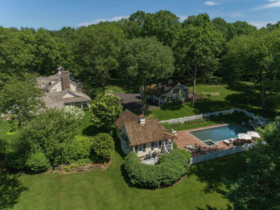 "The 7,000-square-foot center hall colonial at 20 Partridge Hollow is located in a private, gated community with 24-hour security. Its 5.79-acre lot sits adjacent to the 285-acre Audubon property, rendering it particularly private. The ""quintessential country compound"" is listed for $5.85 million. Photo: New England Land Company / ONLINE_CHECK"