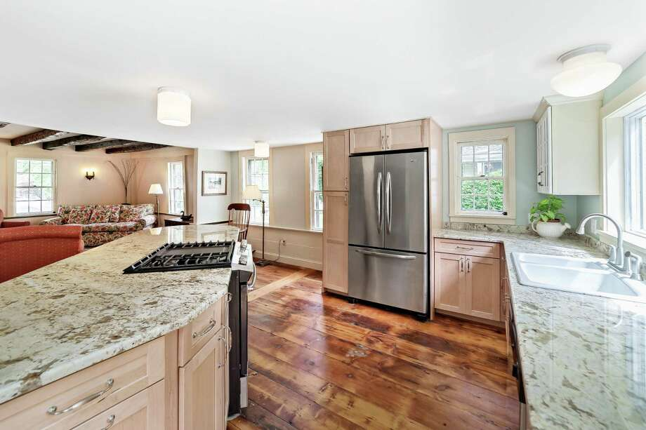 The stunning gourmet kitchen at 111 North St. in Milford features wide plank flooring and a center island. The Sanford Bristol House is listed on The National Register of Historic Places and has been restored and updated by the current owner. Photo: Coldwell Banker Residential Broker / ONLINE_CHECK
