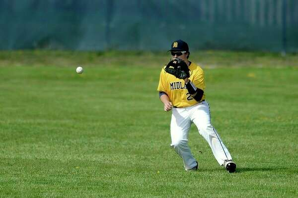 Midland High's Martin Money fields a hit to the outfield in a game against Lapeer in this Daily News file photo.