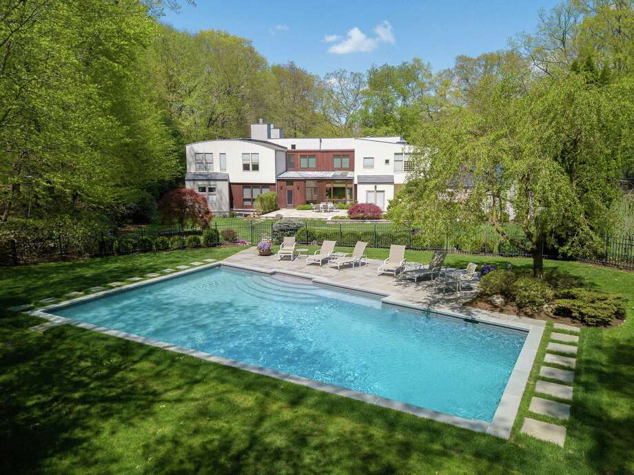 The five-bedroom contemporary at 500 Woodbine Road in Stamford features a Gunite pool, a tennis court and a four-car garage. Photo: Halstead Connecticut / ONLINE_CHECK