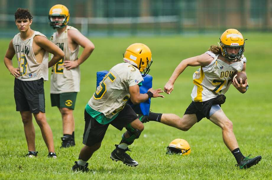 Dow's Chase Perry runs the ball while Ethan Ells defends against him during the Chargers' first football practice of the season on Monday, Aug. 6, 2018 at H. H. Dow High School. (Katy Kildee/kkildee@mdn.net) Photo: (Katy Kildee/kkildee@mdn.net)