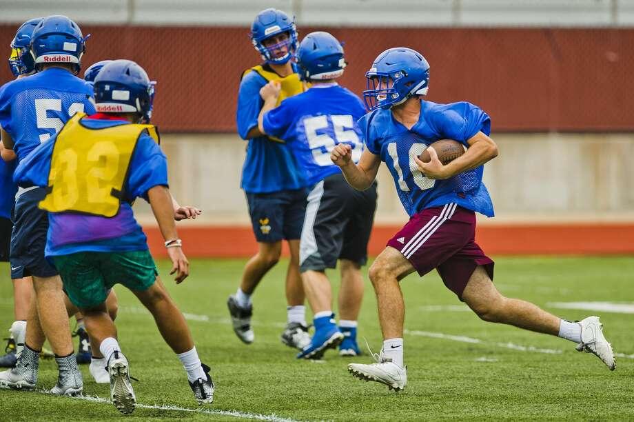 Midland's Christian Gordon runs the ball during the Chemics' first football practice of the season on Monday, Aug. 6, 2018 at Midland High School. (Katy Kildee/kkildee@mdn.net) Photo: (Katy Kildee/kkildee@mdn.net)