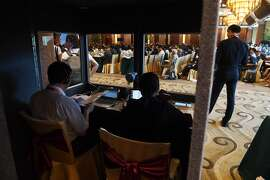 Translators work in a booth as delegates listen to speeches during the opening session of the Belt and Road Forum on Legal Cooperation at the Diaoyutai State Guesthouse in Beijing on July 2, 2018. / AFP PHOTO / GREG BAKERGREG BAKER/AFP/Getty Images