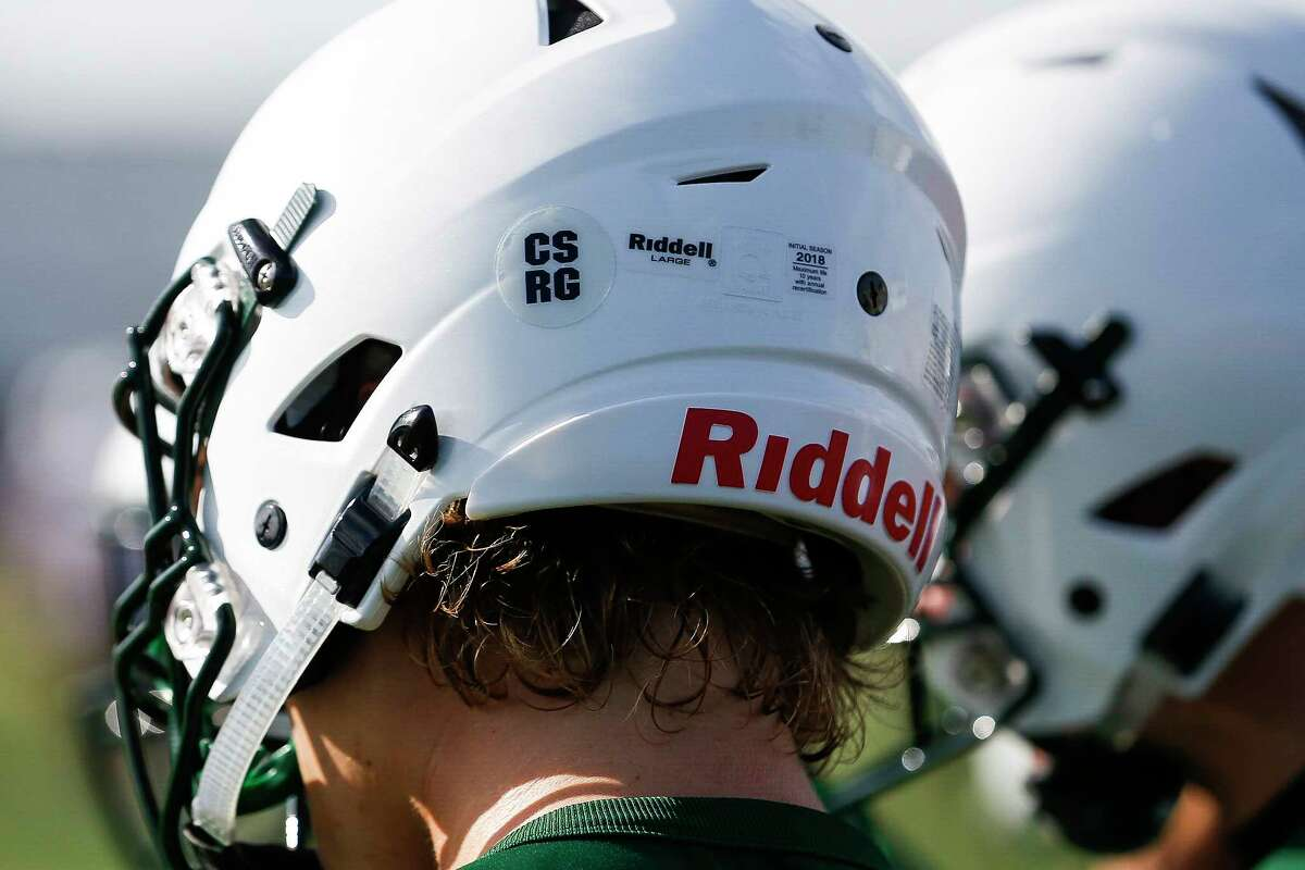 A Santa Fe High School football players makes a catch during the first practice of the year Monday Aug. 6, 2018 in Santa Fe. Players wore stickers displaying the initials of two of the team's players, Christopher Stone and Christian Riley Garcia, who were killed last May during the school shooting that claimed the lives of 10 students and teachers.