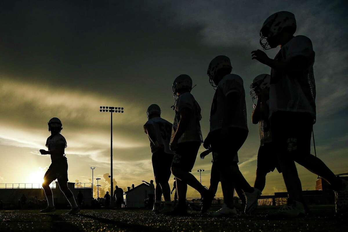 Santa Fe High School football players run through drills during their first practice of the year Monday Aug. 6, 2018 in Santa Fe. Two of the team's players, Christopher Stone and Christian Riley Garcia, were killed last May during the school shooting that claimed the lives of 10 students and teachers.