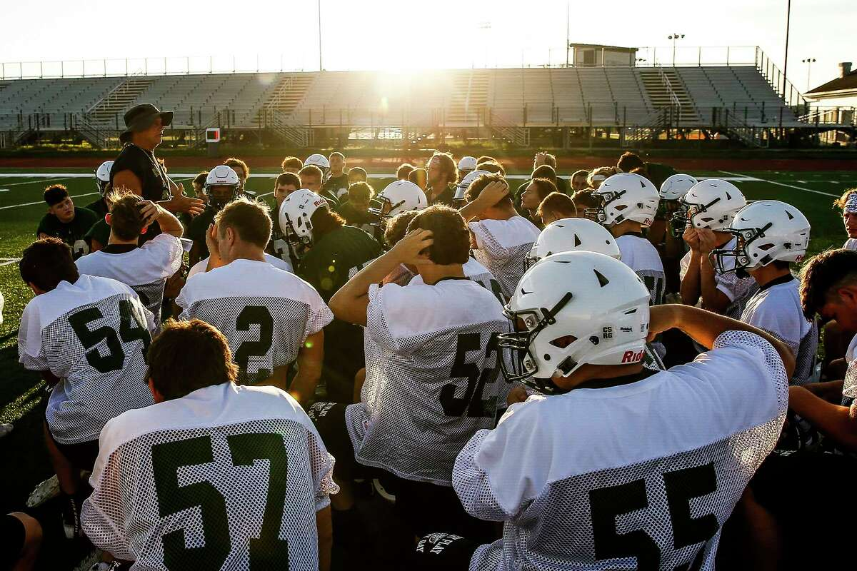 The Santa Fe High School football team huddles up to listen to coach Mark Kanipes during their first practice of the year Monday Aug. 6, 2018 in Santa Fe. Two of the team's players, Christopher Stone and Christian Riley Garcia, were killed last May during the school shooting that claimed the lives of 10 students and teachers.