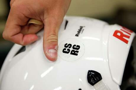 Before the first practice of the year, Santa Fe High School football player Bryce Montemayor places a sticker with the initials of two football players who were killed in the school shooting last May on his helmet. Players Christopher Stone and Christian Riley Garcia were among the 10 students and teachers killed in the shooting.