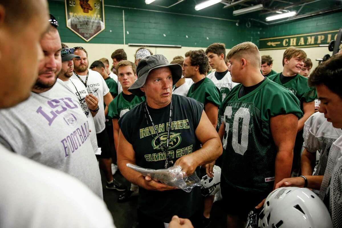 During the first practice of the year, Santa Fe High School football coach Mark Kanipes hands out stickers with the initials of two football players who were killed in the school shooting last May for players to add to their helmets. Players Christopher Stone and Christian Riley Garcia were among the 10 students and teachers killed in the shooting.