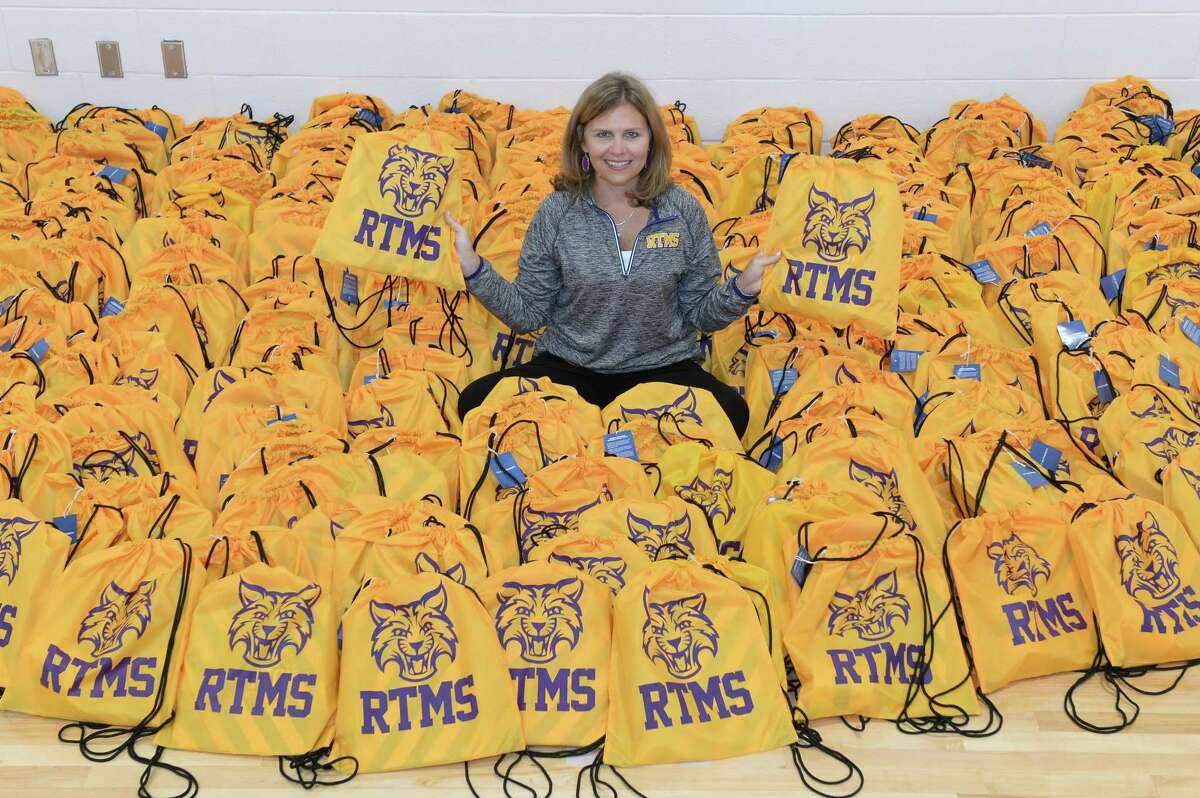 Principal Jeanna Sniffin sits in a sea of backpacks that will be given to students on the first day of school at FBISD's Ronald Thornton Middle School, Missouri City, TX, on August 3, 2018
